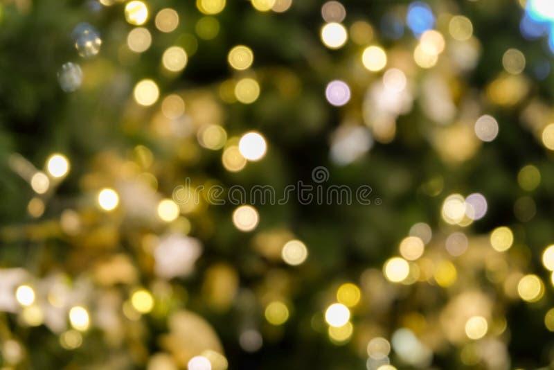 La luce del bokeh dell'albero di Natale nel colore dorato giallo verde, fondo astratto di festa, offusca defocused immagine stock libera da diritti