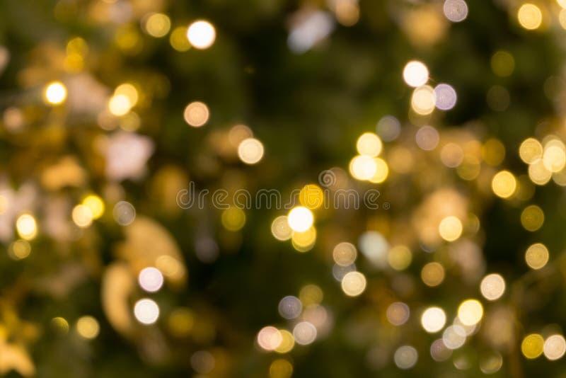 La luce del bokeh dell'albero di Natale nel colore dorato giallo verde, fondo astratto di festa, offusca defocused immagini stock