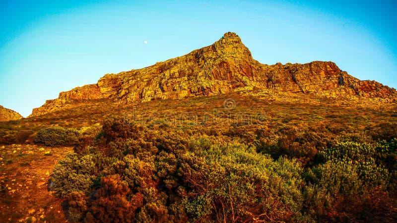 La luce dell'alba colpisce un affioramento della montagna rocciosa fotografia stock