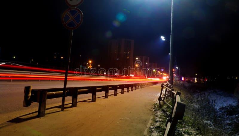 La luce dell'automobile trascina sulla via, fondo della via di notte Foto lunga di esposizione fotografie stock