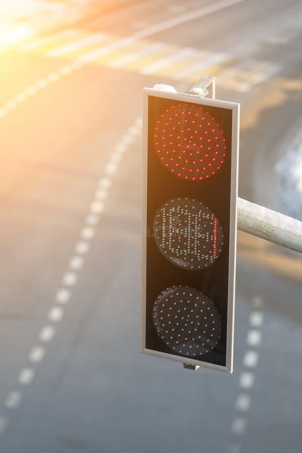 La luce di colore rosso è indicata su un semaforo moderno del LED che appende sopra la strada vuota fotografia stock