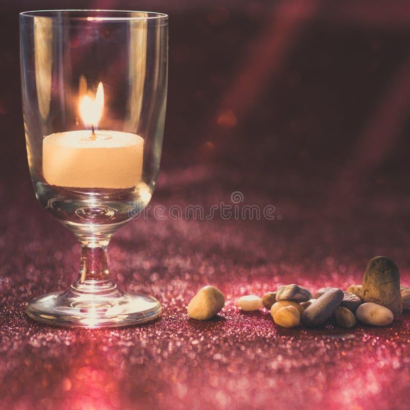 La luce dorata delle candele che bruciano in vetro di vino con effetto e rosso della luce ha offuscato il fondo del bokeh Stile d immagine stock libera da diritti