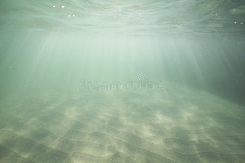 La luce solare che splende attraverso la superficie dell'oceano e che raggiunge il fondale marino come sabbia ? tirata fuori dall fotografie stock libere da diritti