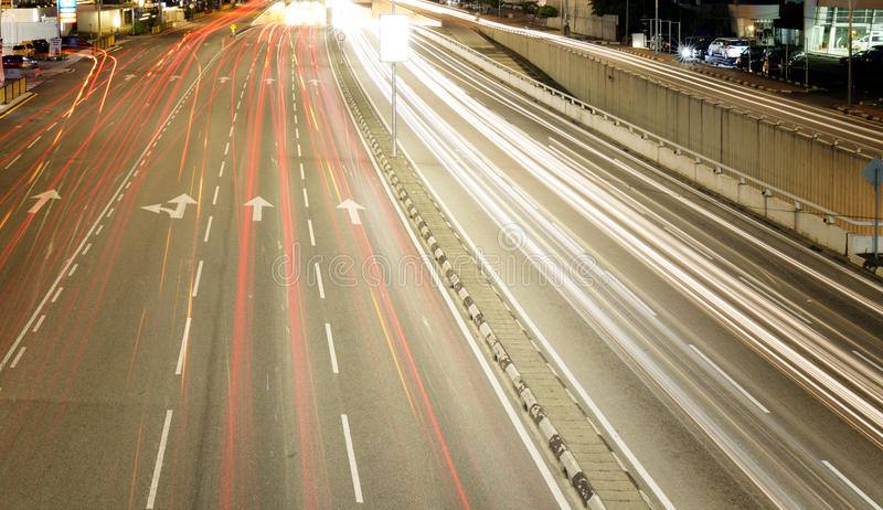 La luce trascina da una strada affollata in una città immagini stock