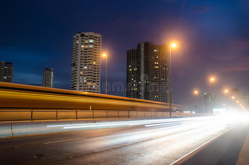 La luce trascina sull'ingorgo stradale moderno del fondo della costruzione immagine stock libera da diritti
