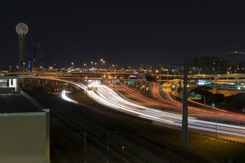 La luce trascina sulla strada principale I-35 a Dallas con la torre della Riunione fotografia stock libera da diritti