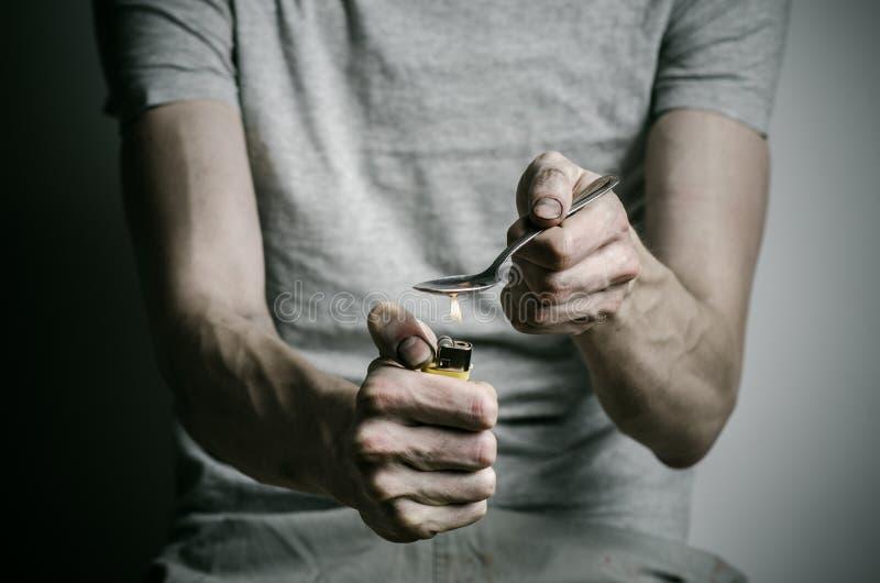 La lucha contra las drogas y tema de la drogadicción: envicie sostener el encendedor de la cuchara y calienta la droga líquida en fotos de archivo