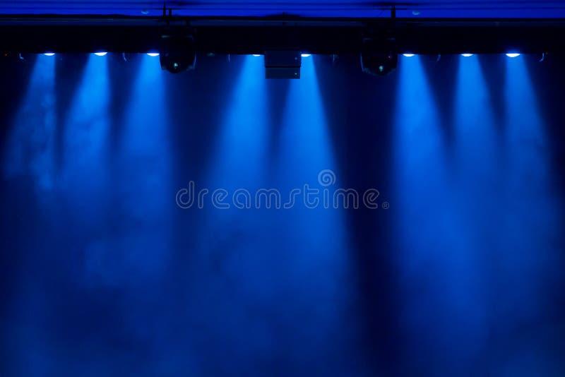 La lumière bleue des projecteurs par la fumée dans le théâtre pendant la représentation photos stock