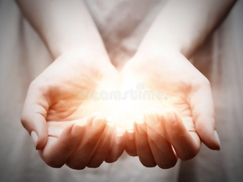 La lumière chez des mains de jeune femme. Partager, donner, offrant, protection image stock