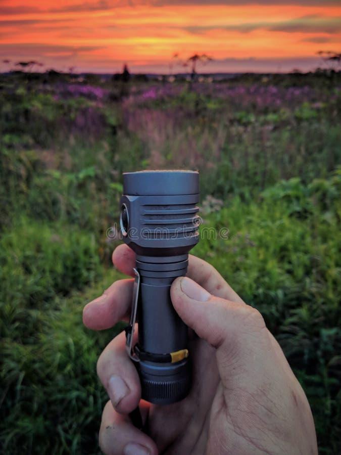 La lumière d'une lampe-torche de main se transforme en coucher du soleil photos libres de droits