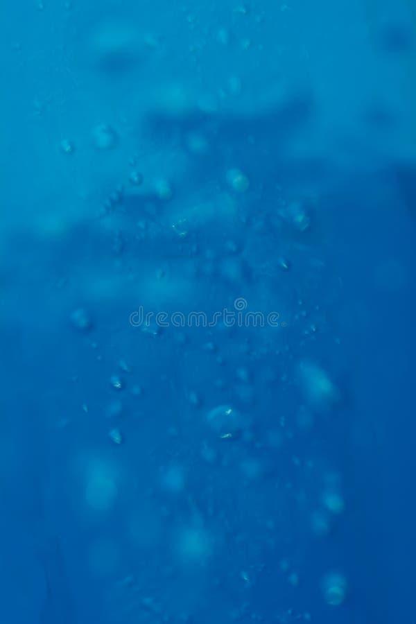 La lumière de fond de tache floue s'est reflétée dans l'eau avec les bulles d'air et le bokeh images stock