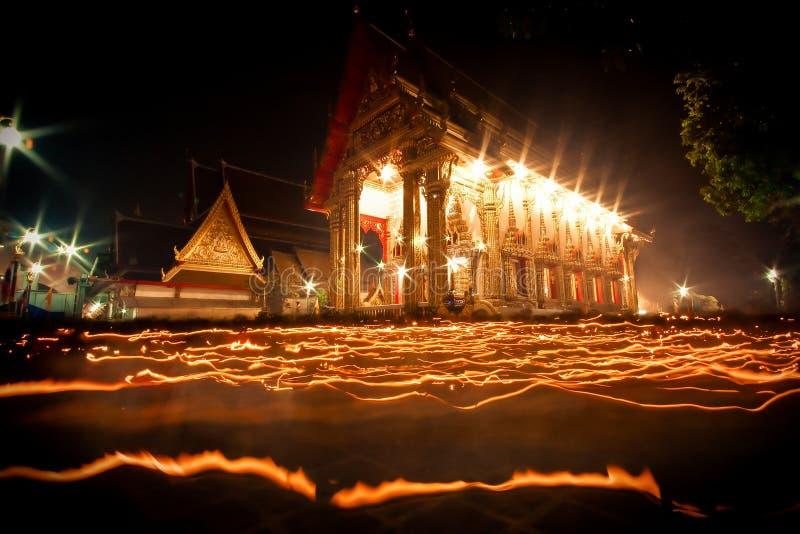 La lumière de la bougie s'est allumée la nuit autour de l'église du bouddhiste prêtée image stock