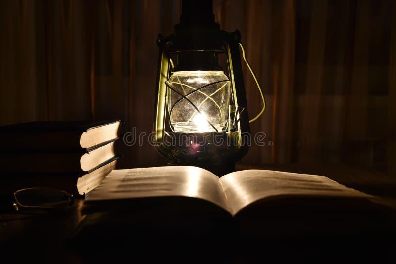 La lumière de la lampe de kérosène et du livre ouvert sur la table images stock