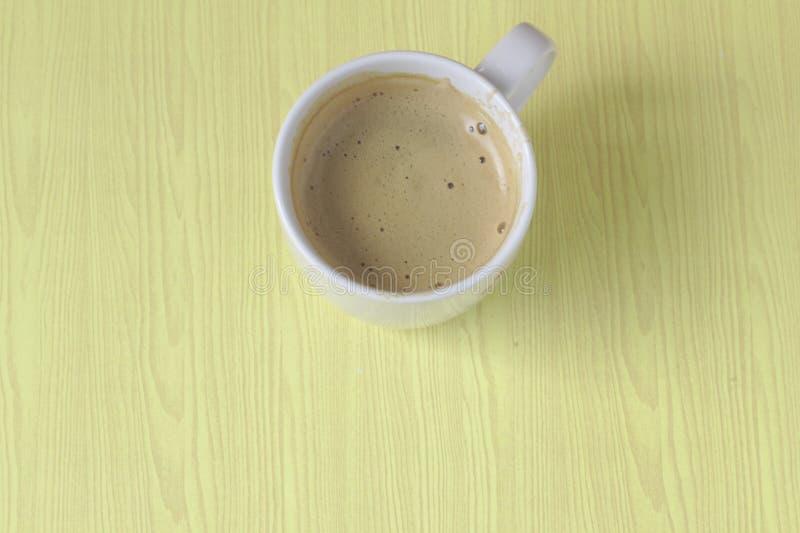 La lumière de matin de tasses de café blanc sur le plancher des bulles en bois jaunes d'un café de table dans un petit déjeuner e images libres de droits