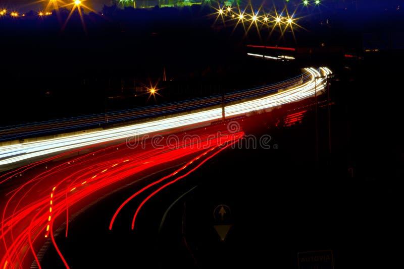 La lumière de véhicule traîne en rouge et le blanc sur la route de nuit photo stock