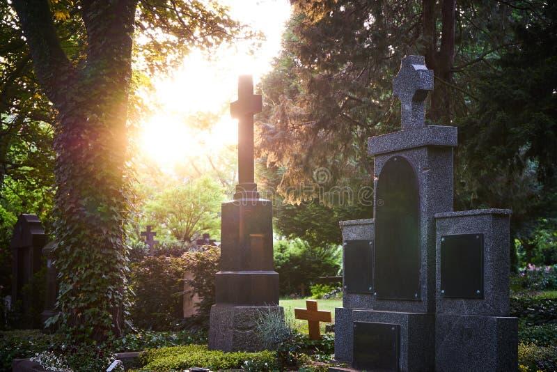 La lumière du soleil brille par les arbres d'un cimetière touchant de vieilles pierres tombales sur un cimetière au coucher du so photos stock