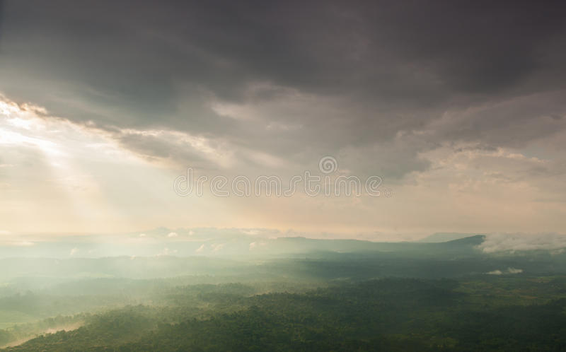 La lumière du soleil brille par les nuages dans les montagnes et la forêt image libre de droits