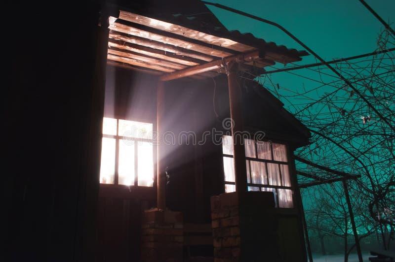 La lumière lumineuse dans la fenêtre, des choses étranges se produisent dans une maison mystérieuse, photos libres de droits