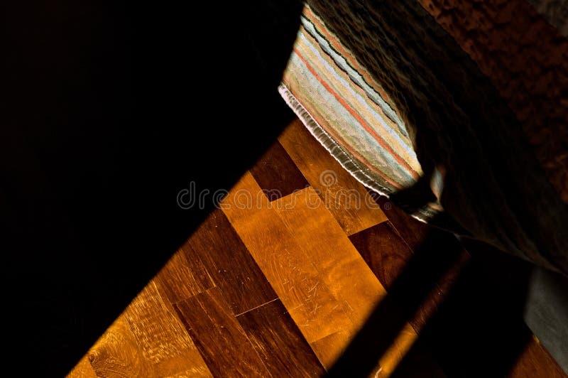 La lumière qui filtre à travers la fenêtre illumine le parquet et une bande de lit rayonnant Italie, Europe photo libre de droits