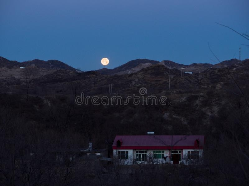 La luna aumenta dalla cima immagine stock