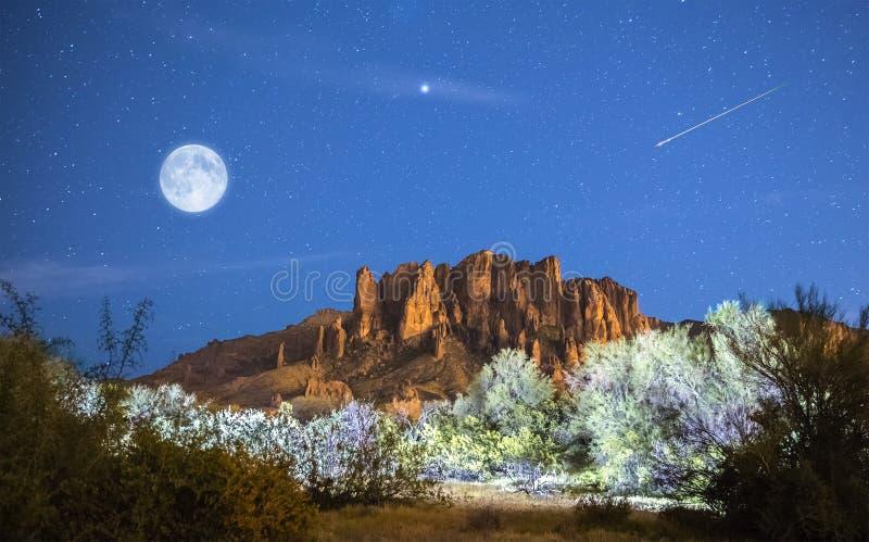 La luna aumenta sopra le montagne di superstizione fotografia stock