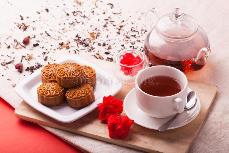 La luna del chino tradicional se apelmaza en el ajuste de la tabla con la taza de té foto de archivo libre de regalías