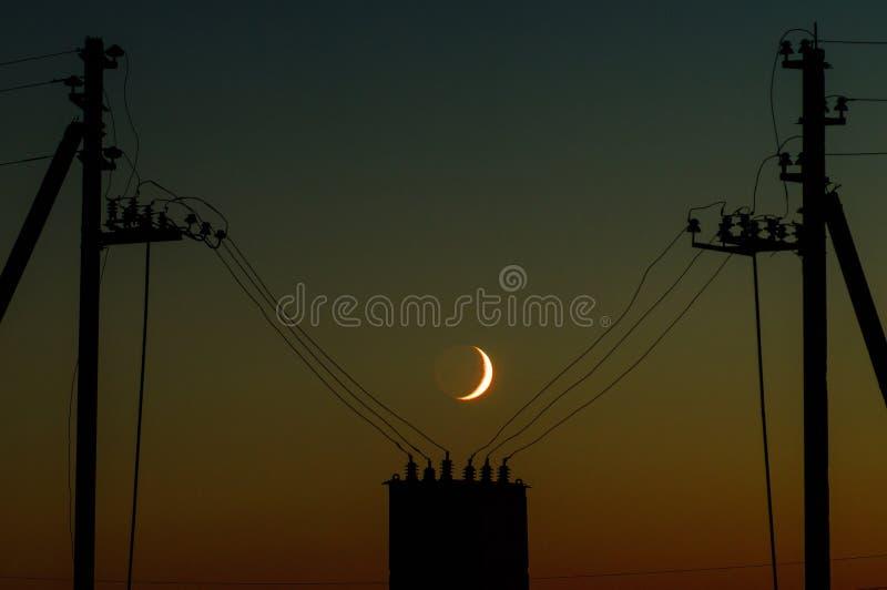 La luna joven con una línea eléctrica imagen de archivo