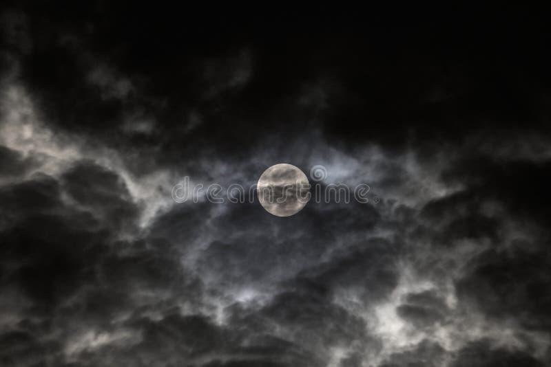 La Luna Llena según lo visto detrás de las nubes rápidas imagenes de archivo