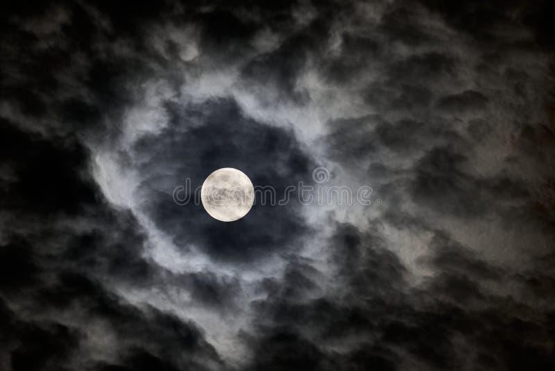 La Luna Llena según lo visto a través de las nubes rápidas foto de archivo