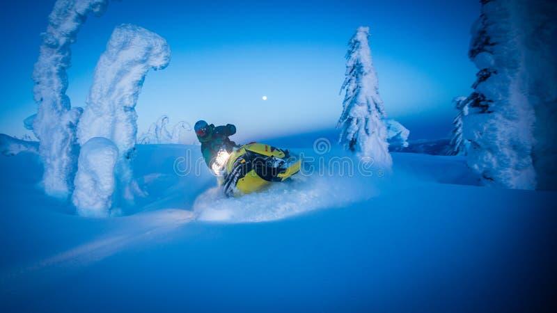 La Luna Llena sobre las montañas nevosas como moto de nieve talla a través imagen de archivo