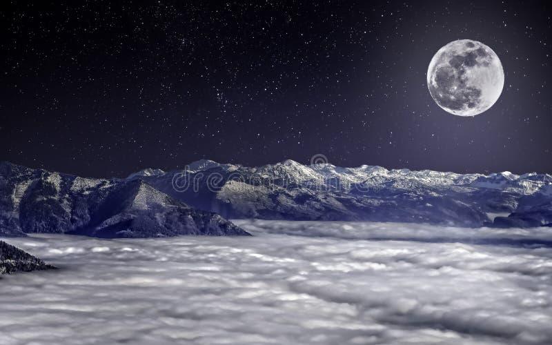 La Luna Llena sobre las montañas nevosas, sobre las nubes, debajo del cielo estrellado fotos de archivo