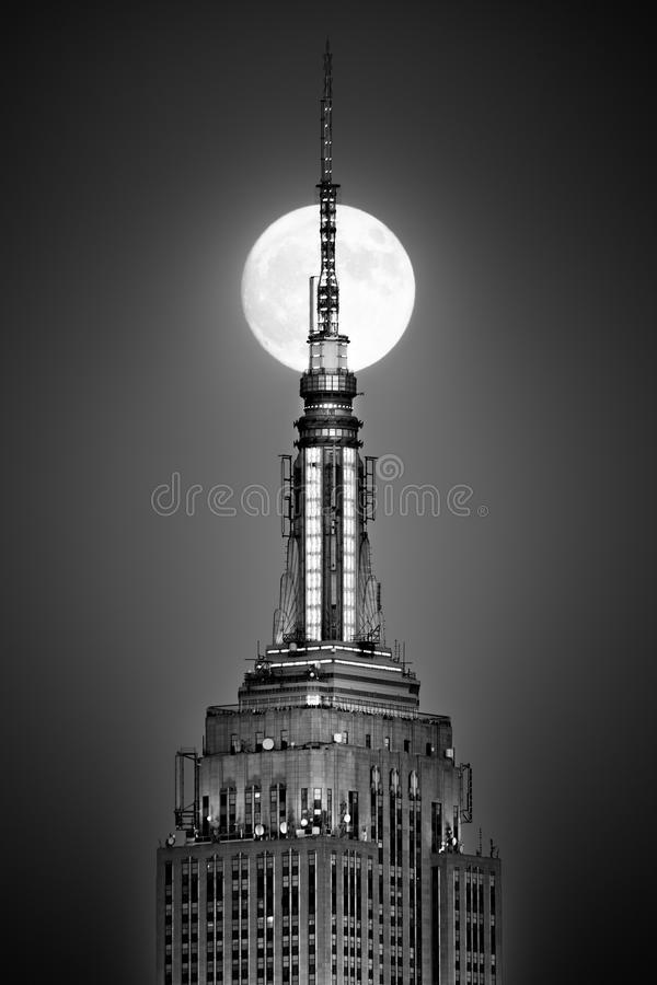 La Luna Llena sube y alinea con el top del Empire State Building fotos de archivo libres de regalías