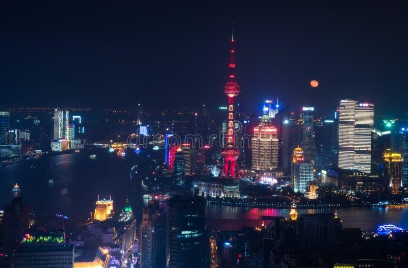La luna piena aumenta dietro l'orizzonte di Pudong fotografia stock libera da diritti