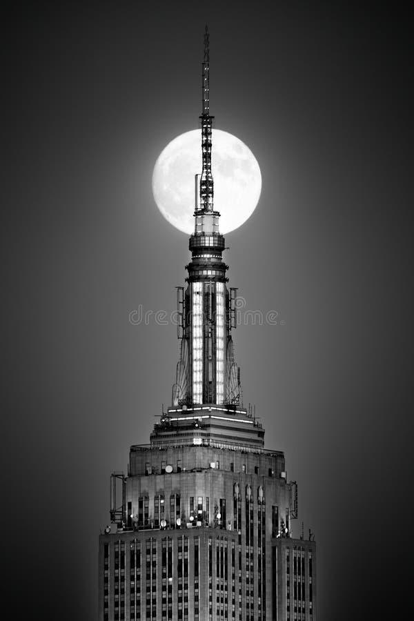 La luna piena aumenta ed allinea con la cima dell'Empire State Building fotografie stock libere da diritti