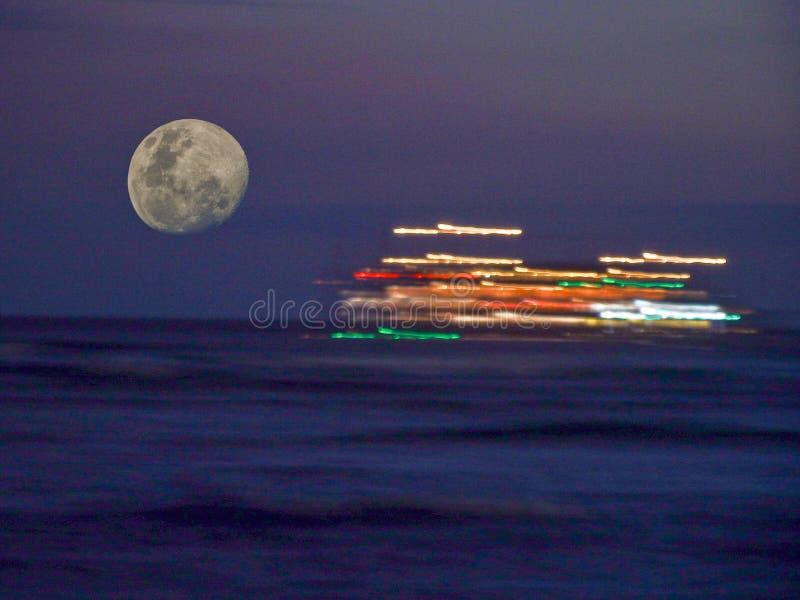La luna piena aumenta a sinistra dell'acceso brillantemente passando la nave immagine stock libera da diritti