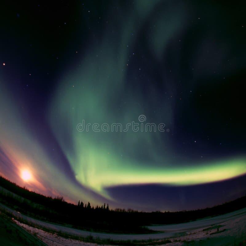 La luna piena incontra l'aurora Borealis fotografie stock libere da diritti