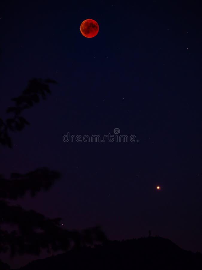 la lune et la planète rouges verticales de sang de pleine lune trouble comme grande étoile image stock