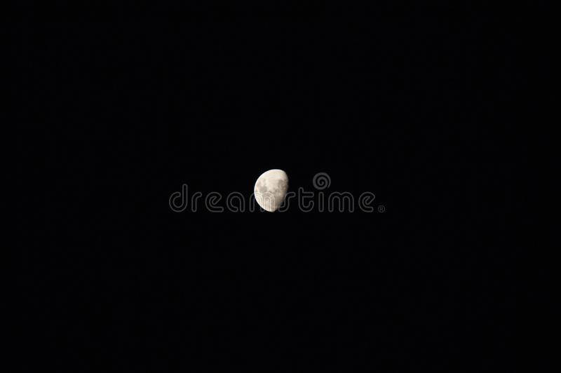 La lune isolée dans un ciel bleu images libres de droits