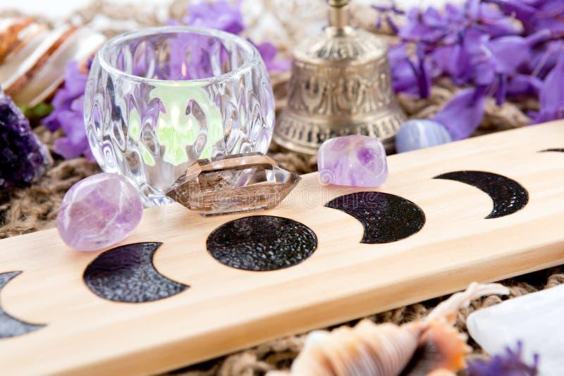 La lune païenne de sorcière met l'autel en phase avec le cristal et les fleurs photographie stock