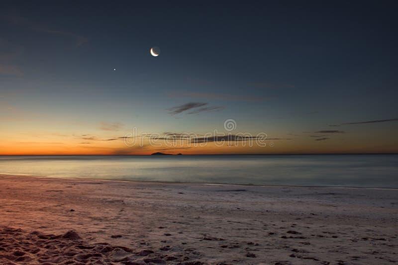 La lune se lève au-dessus de la plage image libre de droits
