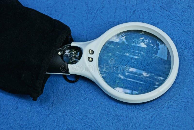 La lupa en una caja negra miente en una tabla azul fotografía de archivo