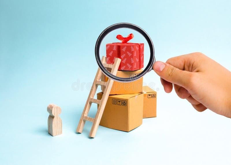 La lupa está mirando al niño se coloca cerca de una caja de regalo en una pila de cajas El concepto de encontrar el regalo perfec fotografía de archivo