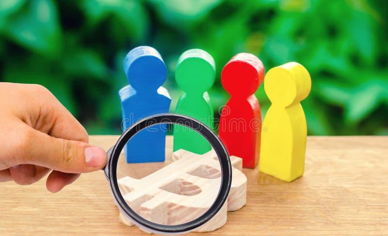 la lupa está mirando cuatro figuras multicoloras de la gente rodea una figura del bitcoin Conducta conceptual de actividades fotos de archivo
