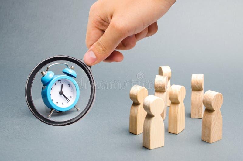 La lupa est? mirando el reloj azul Muchedumbre de miradas de la gente en el reloj Encadenan a la gente de la atenci?n al reloj imagen de archivo