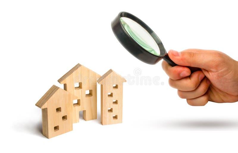 La lupa está mirando las casas de madera en un fondo blanco El concepto de precios en aumento para contener o el alquiler crecimi imágenes de archivo libres de regalías