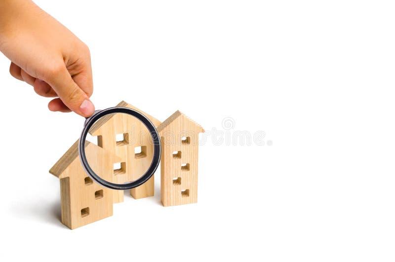 La lupa está mirando las casas de madera en un fondo blanco El concepto de precios en aumento para contener o el alquiler crecimi imagen de archivo