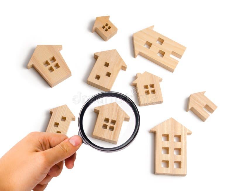 La lupa está mirando las casas de madera en un fondo blanco El concepto de precios en aumento para contener o el alquiler Crecimi fotos de archivo libres de regalías