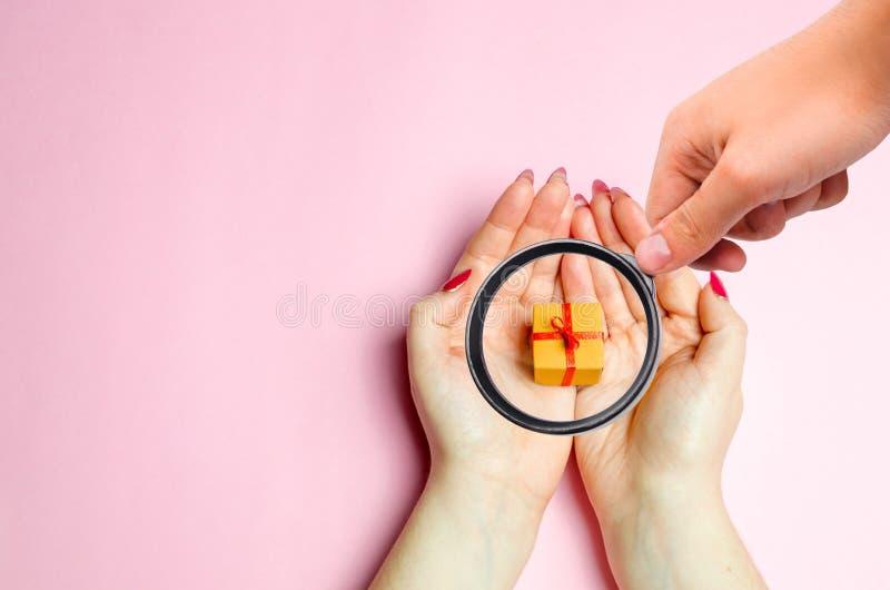 La lupa está mirando a las muchachas que las manos sostienen un regalo Presentes para su amado el día de tarjeta del día de San V fotos de archivo