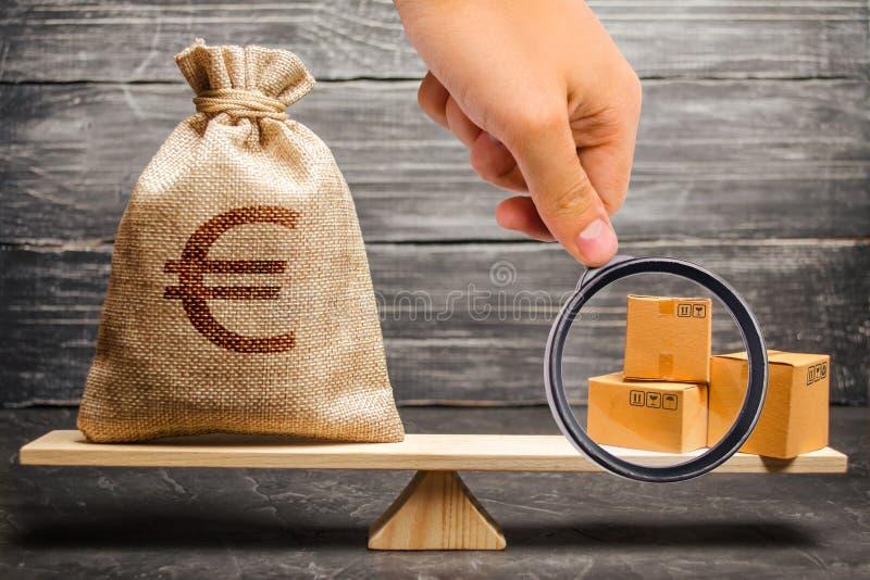 La lupa está mirando un bolso del dinero euro y un manojo de cajas en las escalas Relaciones económicas entre los temas imagen de archivo libre de regalías