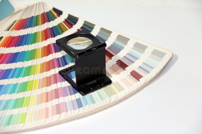 La lupa y el arco iris de la casilla negra muestrean el catálogo de la paleta de colores foto de archivo libre de regalías
